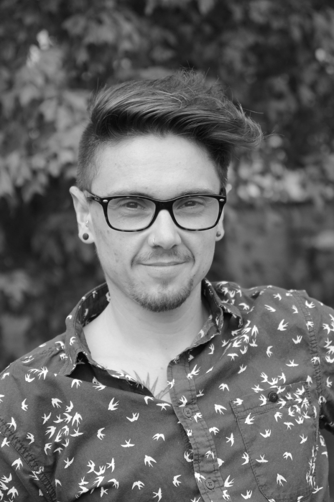 Black and white photo of Chris outside in front of trees. They are looking toward the camera wearing glasses and a shirt with tiny birds printed on it.