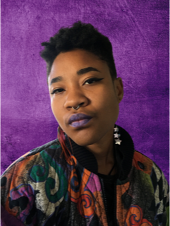 Picture of J. Nyla in front of a purple background tilting their head to the left and looking at the viewer. They are wearing purple lipstick and a mutlicolored top with three starts on the left collar.