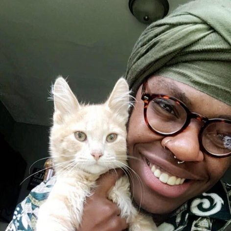 Yante is smiling and holding a kitten up to his face. He wears glasses and an olive green head wrap.